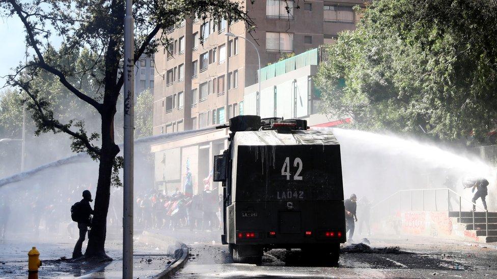 Tanque lanzando agua para dispersar a los manifestantes