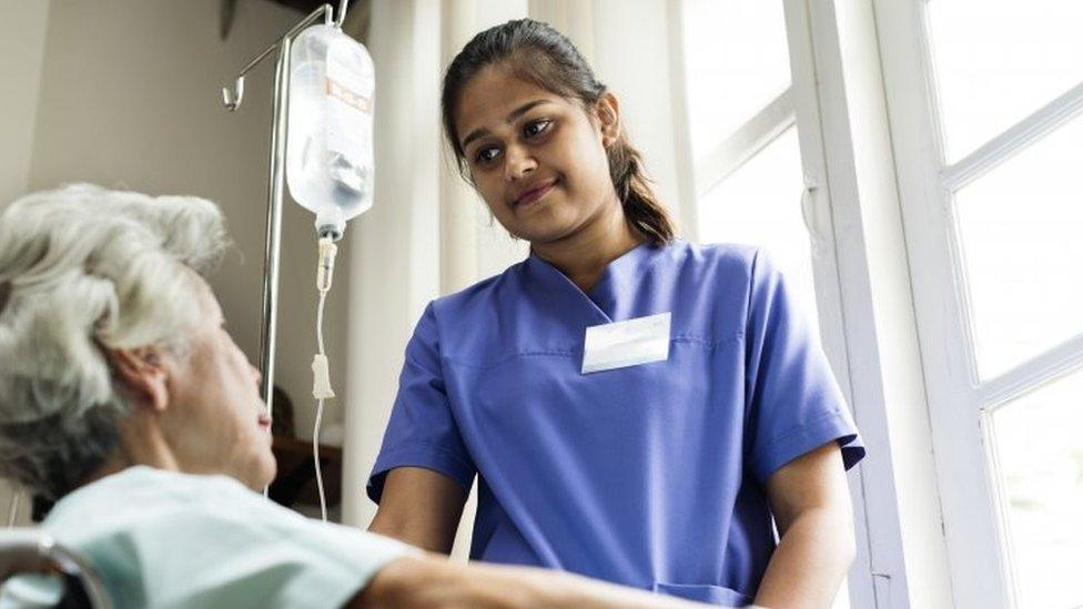 Nurse tends to patient