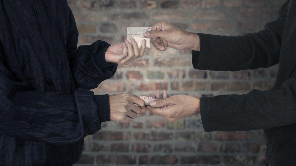 Personas intercambiando dinero por una bolsa con cocaína