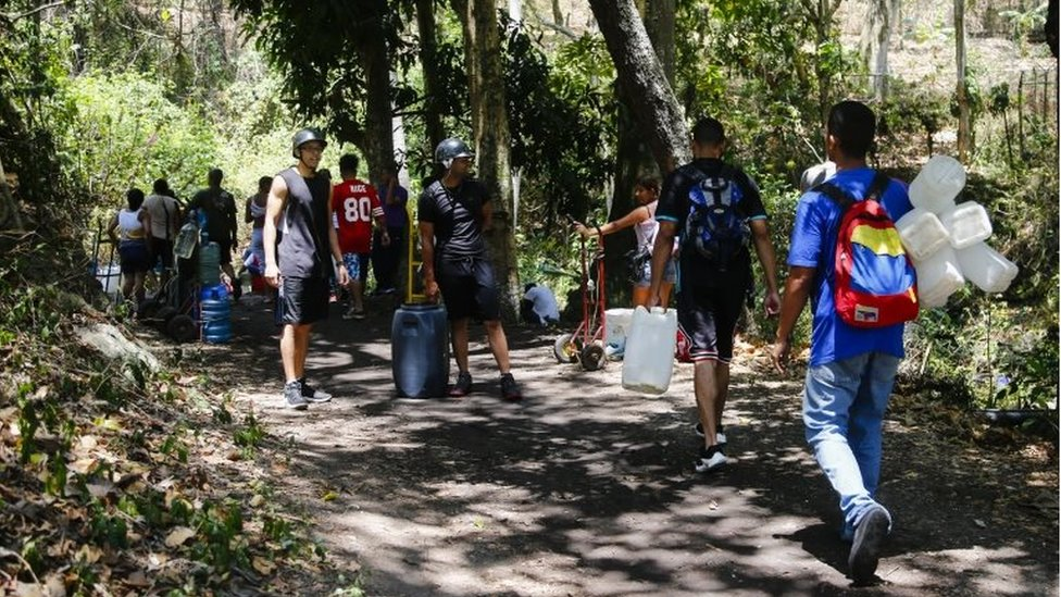 People walk with tanks and bottles to fill them with water that comes from the mountain during blackouts, which affects the water pumps on March 12, 2019 in Caracas, Venezuela.