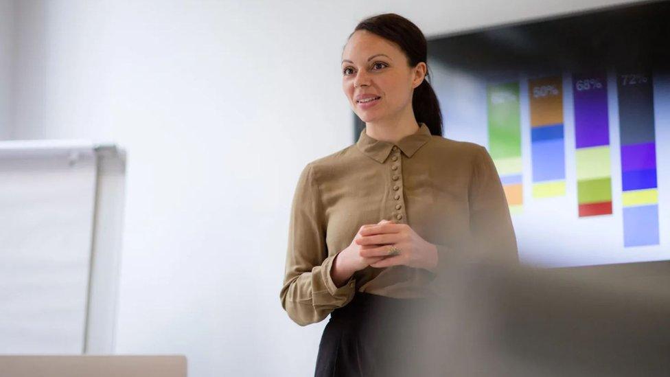 Una mujer con las manos cruzadas en una oficina.