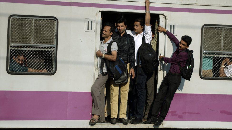 ट्रेन के दरवाज़े पर लटके यात्री