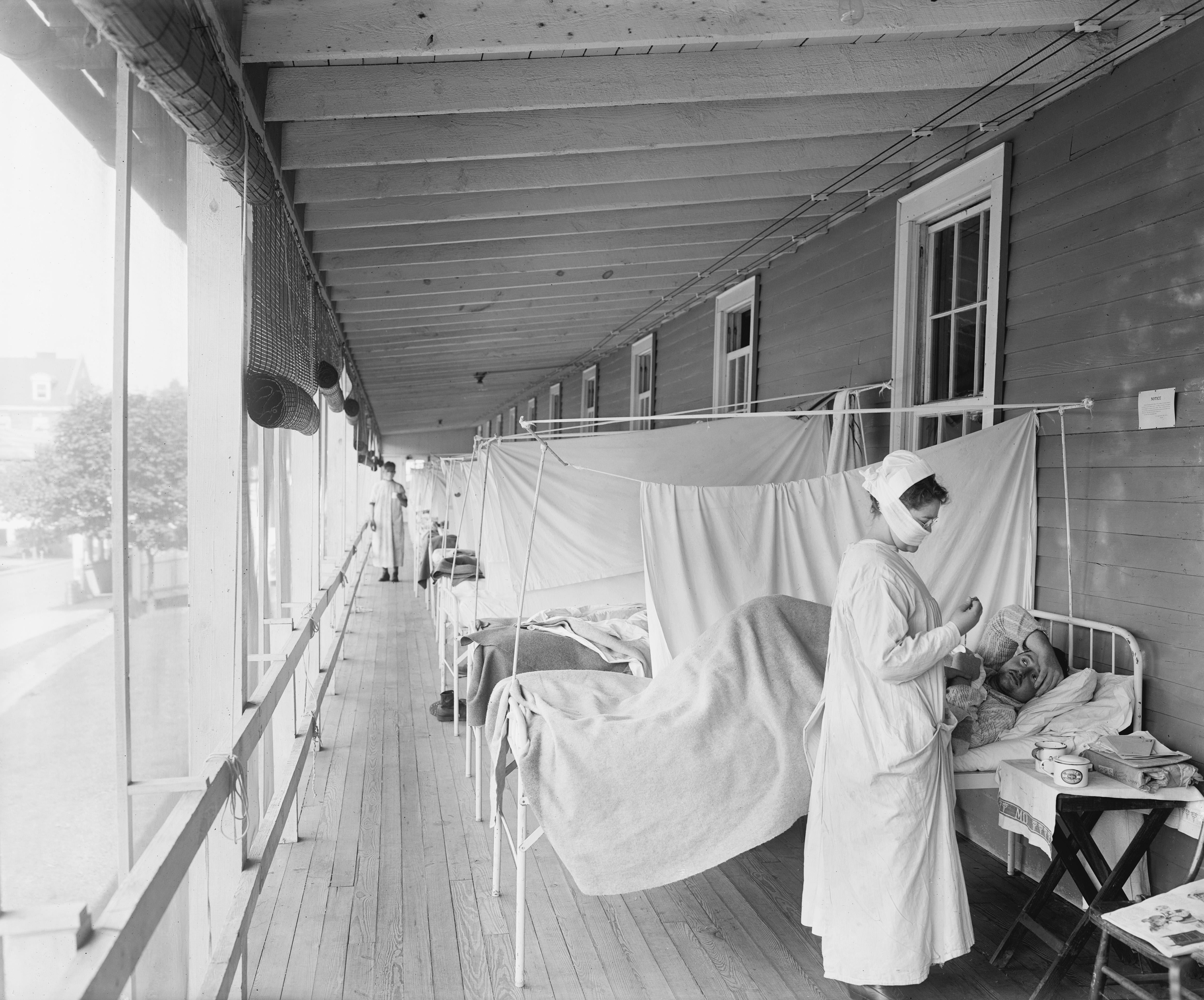 Maske takarak hastasını tedavi eden bir hemşire.