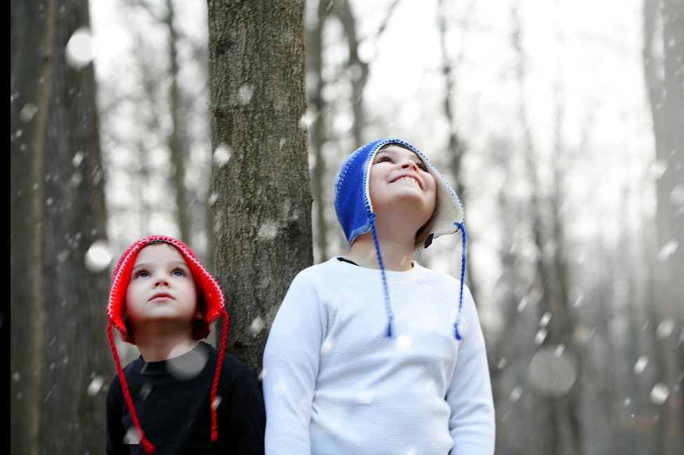 Two children in the woods while snowing