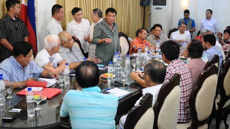 Rodrigo Duterte (centre) speaking to his cabinet - all men, in the picture - around a table in a room in Davao, 31 May 2016.