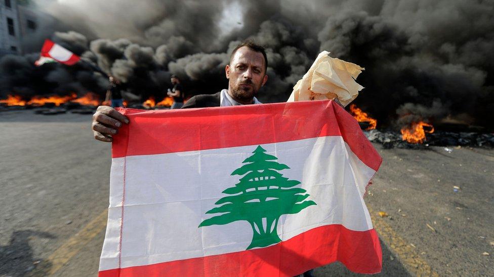 متظاهر يحمل علم لبنان خلفه حاجز من الإطارات المطاطية المشتعلة على الطريق الرابطة بين بيروت ومدينة طرابلس شمالا يوم الجمعة الثامن عشر من أكتوبر تشرين الأول