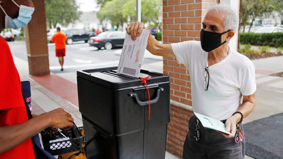Man in a black face mask returns his mail-in ballot