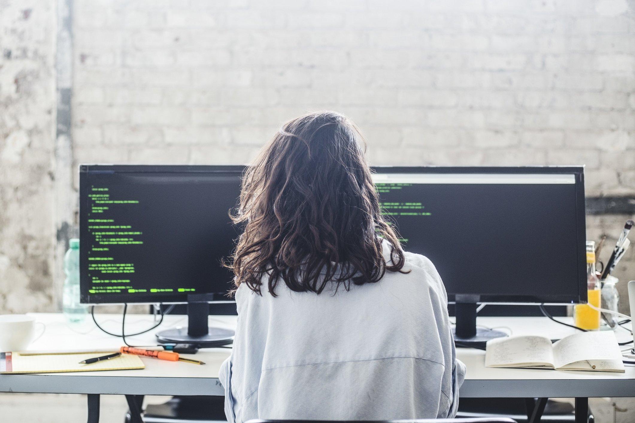 Una joven frente a dos computadoras