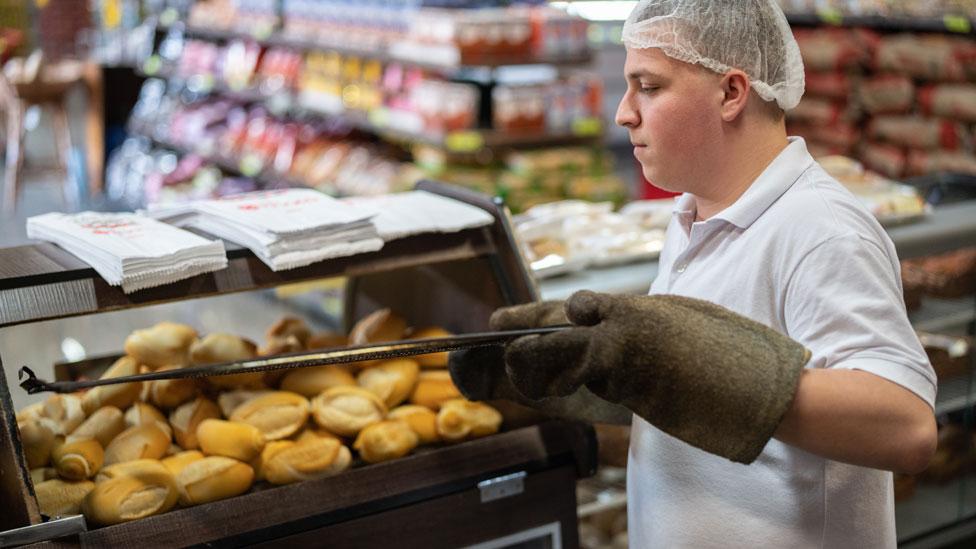 Panadero sacando pancitos de un horno eléctrico en un supermercado