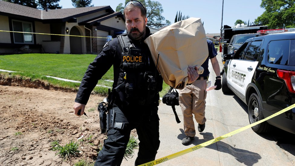 A police officer removes evidence from the home of Joseph Deangelo in Citrus Heights, California, April 26, 2018