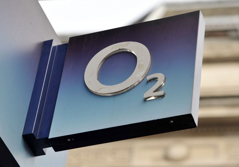 Mobile phone with screen showing Telefonica in front of O2 store