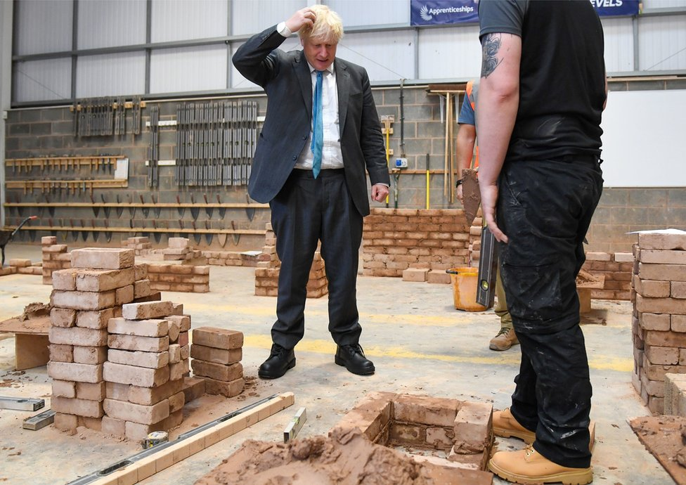 Prime Minister Boris Johnson is shown how to build a brick wall
