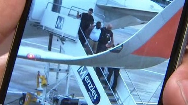 The man being escorted off the plane by police