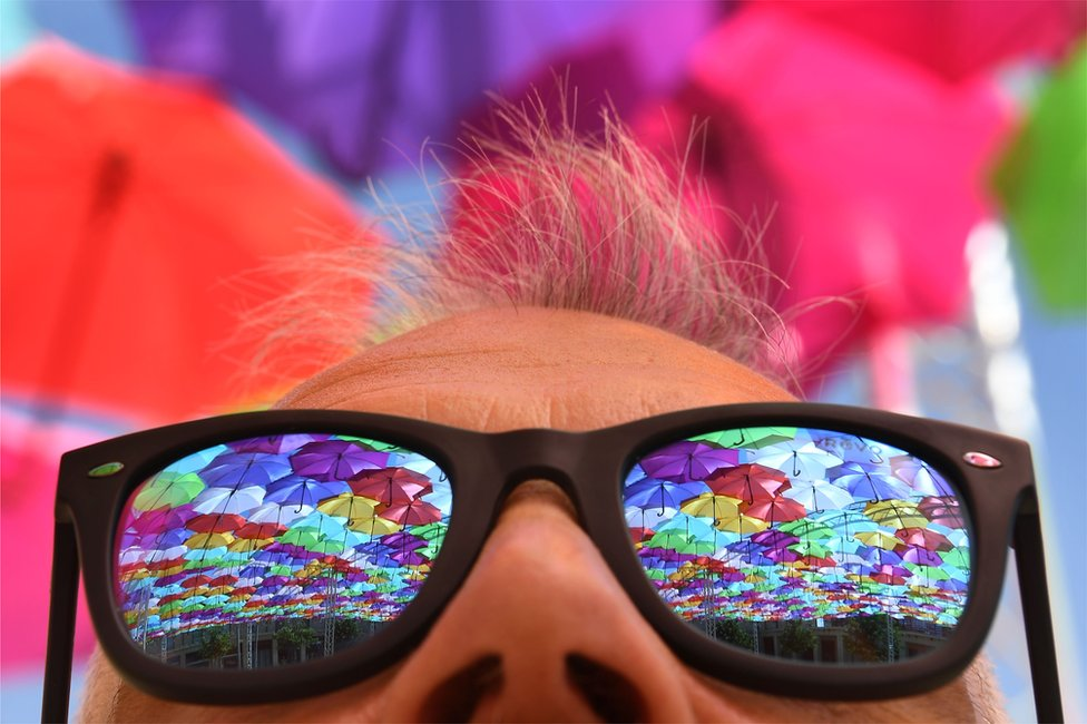 Kišobrani u odsjaju naočara za sunce