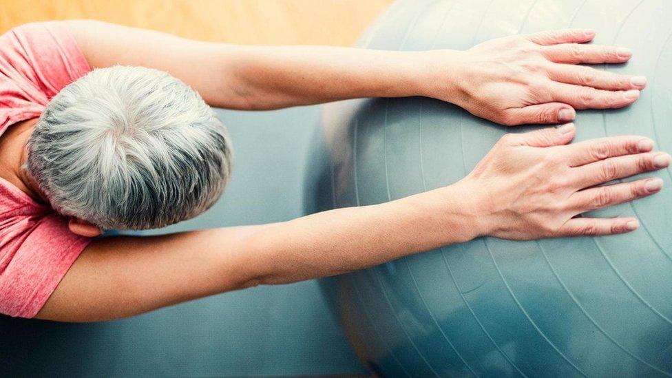 Persona estirándose con una pelota inflable.