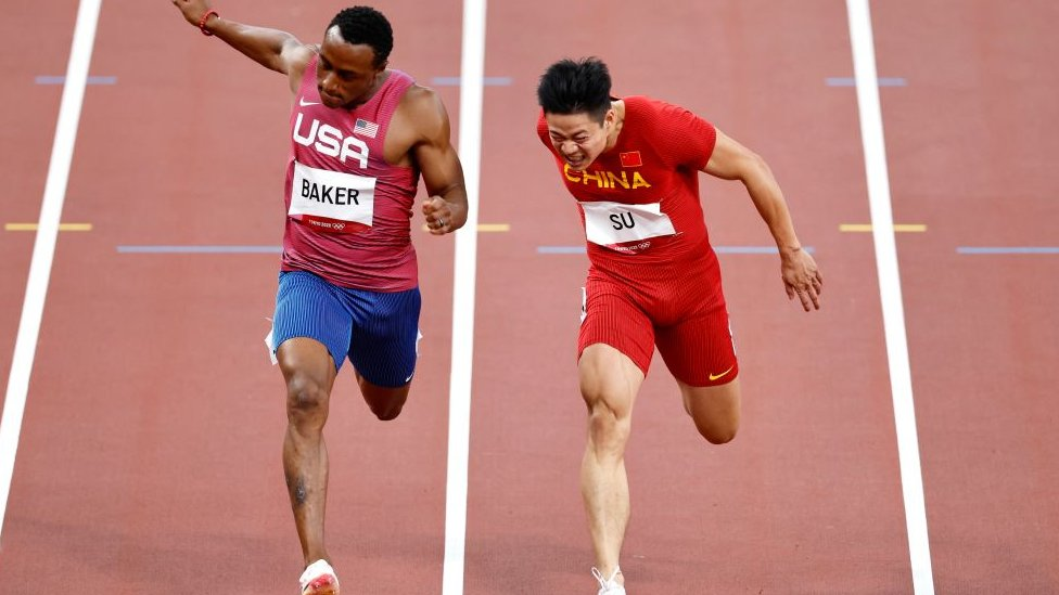 Ronnie Baker of United States and Su Bingtian of China compete in the Men's 100m final at the Tokyo Games