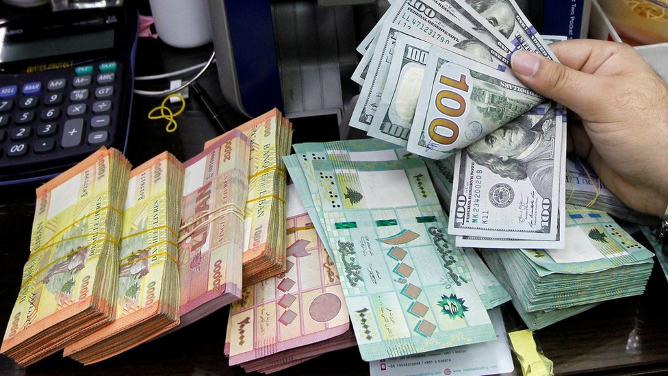 A man counts US dollars next to Lebanese pounds at a foreign exchange shop in Beirut, Lebanon (24 April 2020)