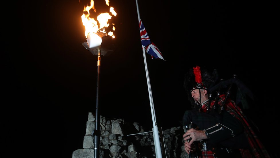 David Danks, of the City of Leeds pipe band, plays as a flame burns at Conisbrough Castle in South Yorkshire