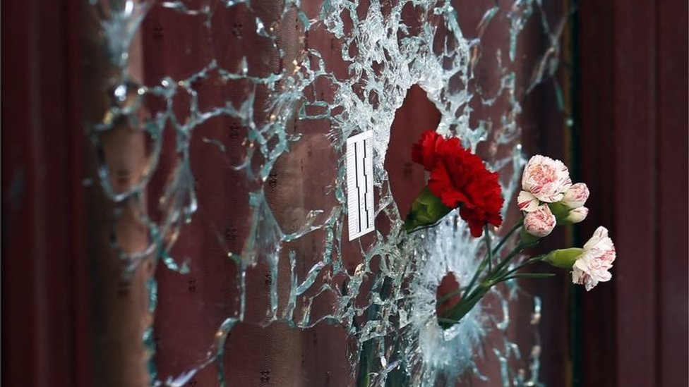 Flowers in a window shattered by a bullet at the Carillon cafe - one of the sites of the 13 November attacks in Paris
