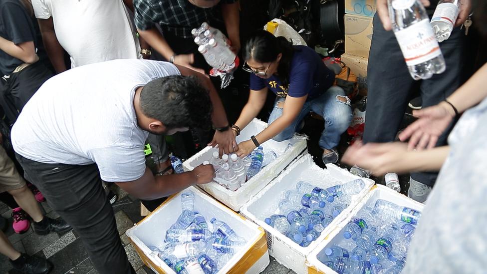 少數族群市民在重慶大廈大門向參加遊行途經的人士派發瓶裝水。