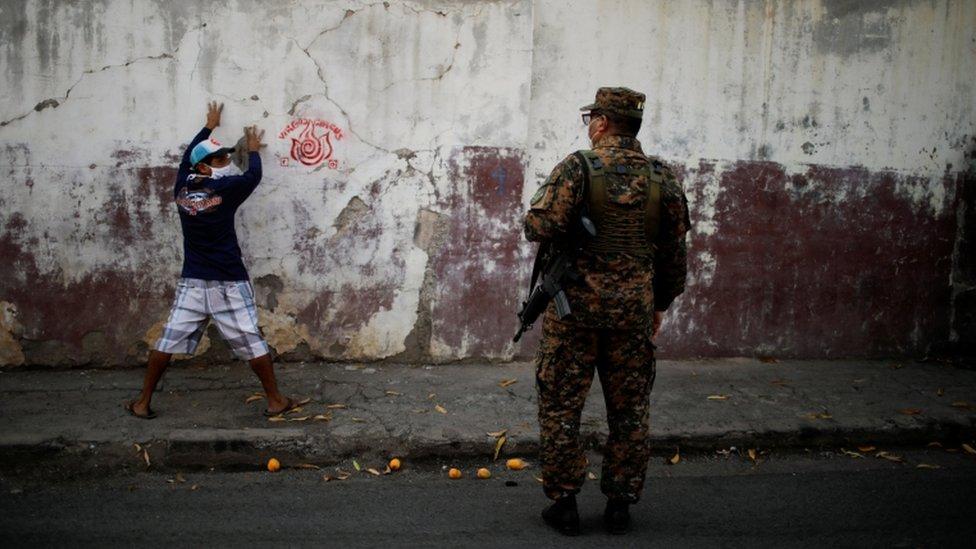 Un miembro del ejército de El Salvador detiene a una persona.