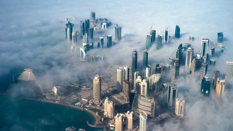 An aerial view of high-rise buildings emerging through fog covering the skyline of Doha