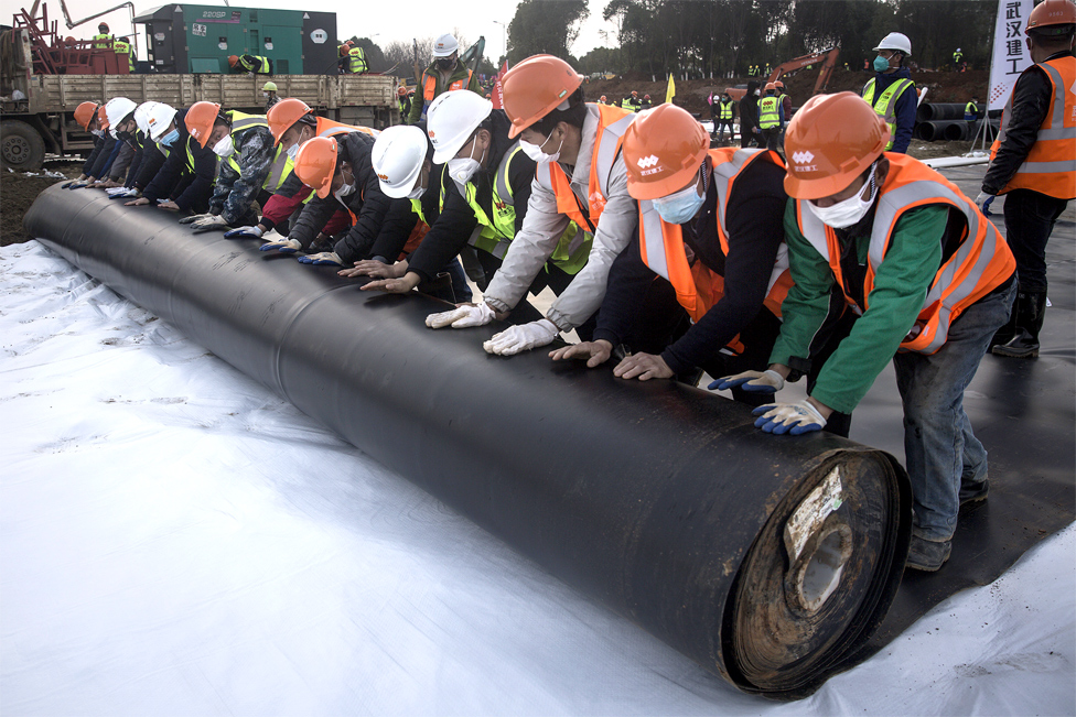 Construction workers roll out damp proof lining