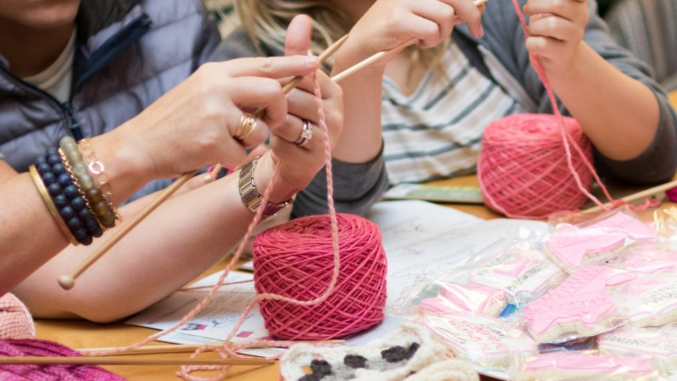 Women's hands can be seen starting a fresh knit from two balls of bright pink yarn