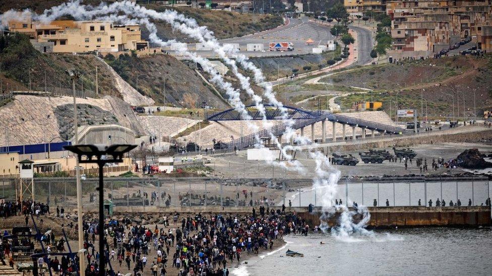 Pasukan keamanan Spanyol menembakkan gas air mata melintasi pagar perbatasan ketika para migran Maroko berkumpul di kota utara Fnideq untuk mencoba melintasi perbatasan.