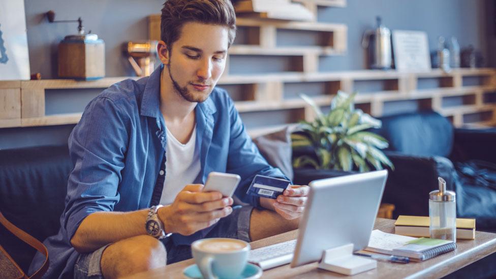 Hombre joven viendo su celular frente a un computador