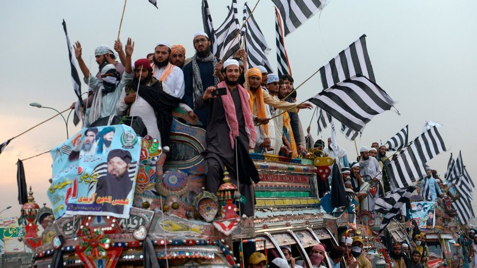 """Supporters of the Islamist Jamiat Ulema-e-Islam (JUI-F) wave party flags atop a vehicle as they take part in an anti-government """"Azadi (Freedom) March"""" towards Islamabad, from Peshawar on October 31, 2019"""