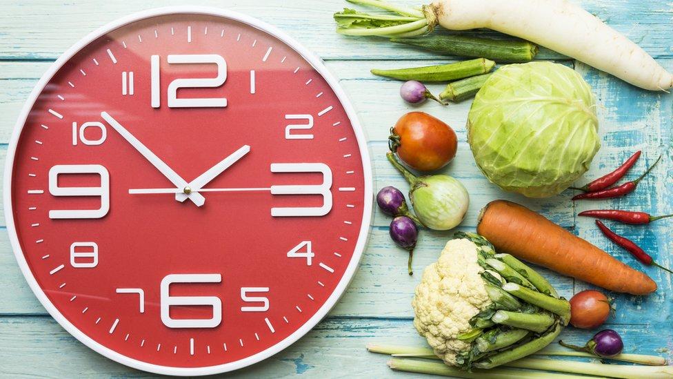 Reloj grande junto a verduras