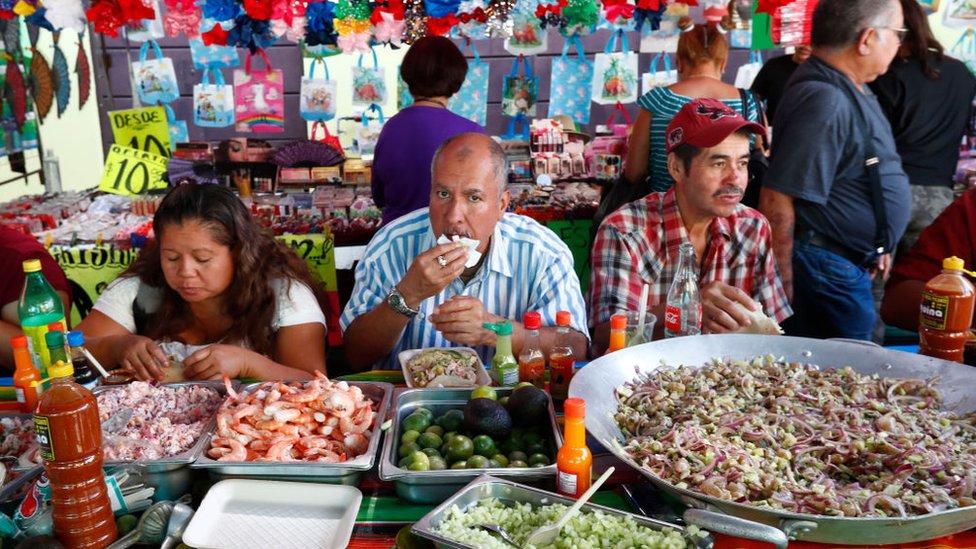 Mexicanos comiendo en un mercado de Guadalajara