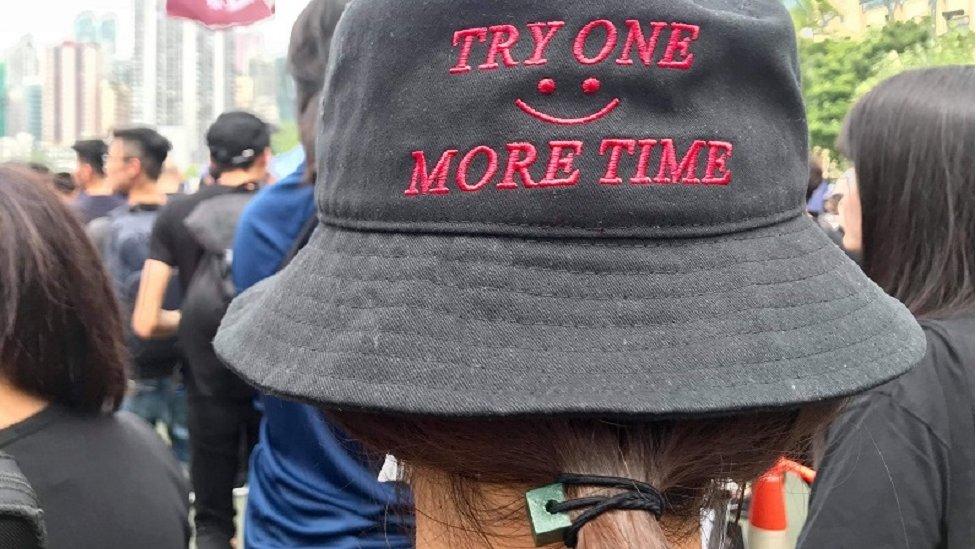 阿依戴帽、戴口罩參加遊行,與周圍的人講廣東話。