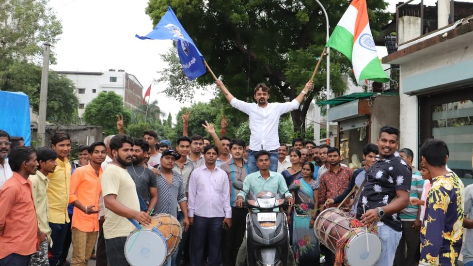Ambedkar Vichar Manch activist celebrating with drums and flags.