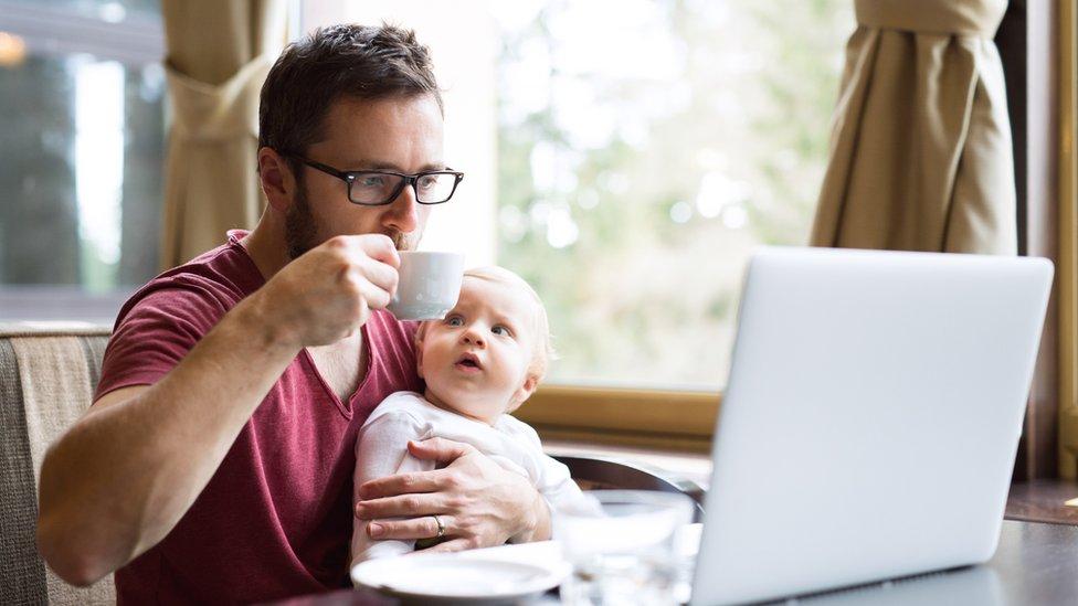 Hombre tomando un café, con un bebé en brazos frente a una computadora.