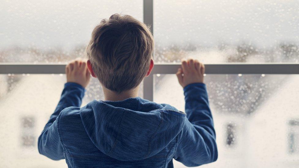 Niño mira por la ventana.