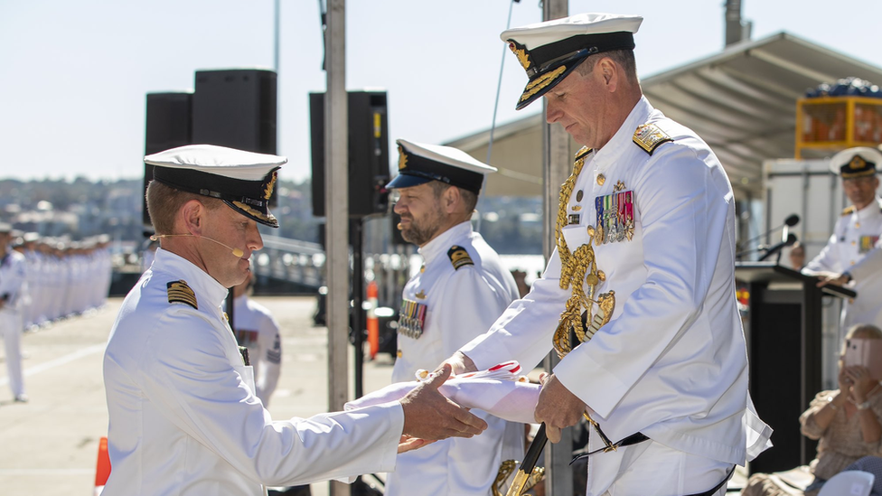 Australian naval officials conduct a ceremony at the commissioning of HMAS Supply