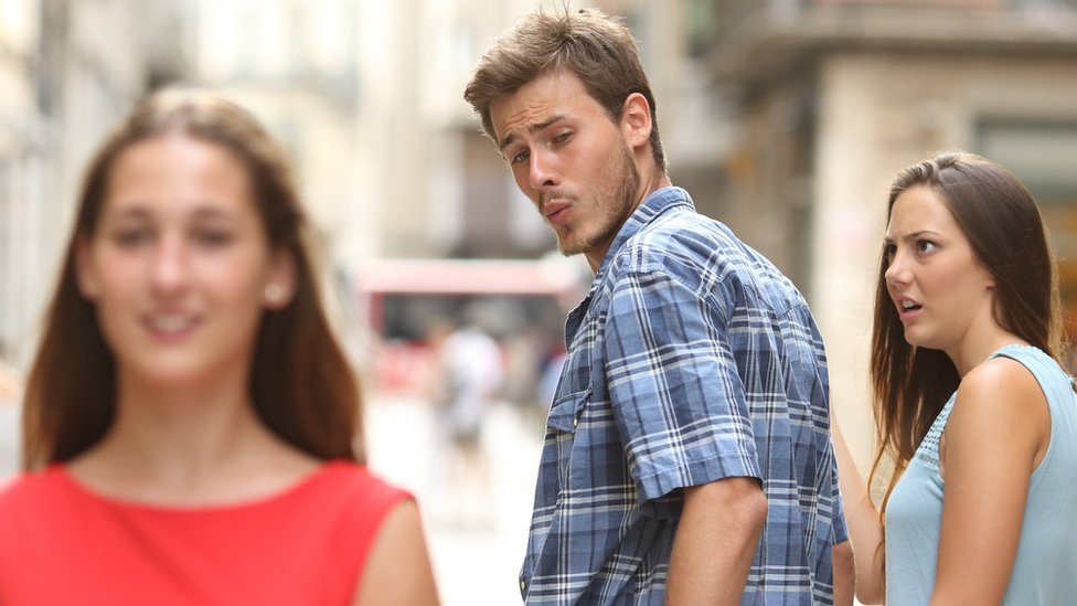 A distracted boyfriend looks at another woman while his girlfriend looks on in disgust