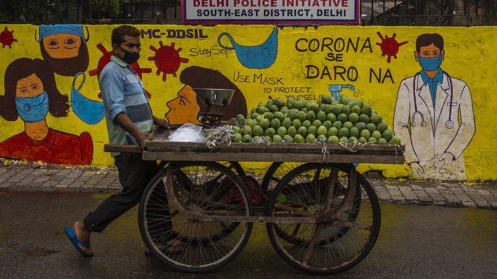 yeni delhi'de maske takan bir seyyar satıcı.