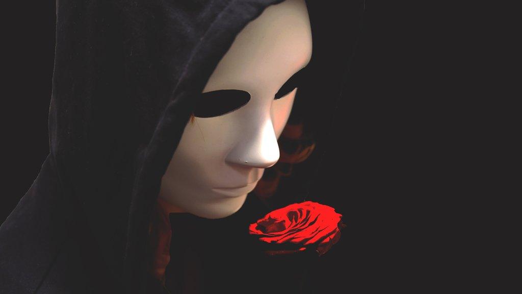 Persona con máscara, capa y rosa