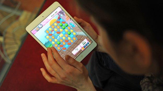 Woman plays Candy Crush Saga on iPad
