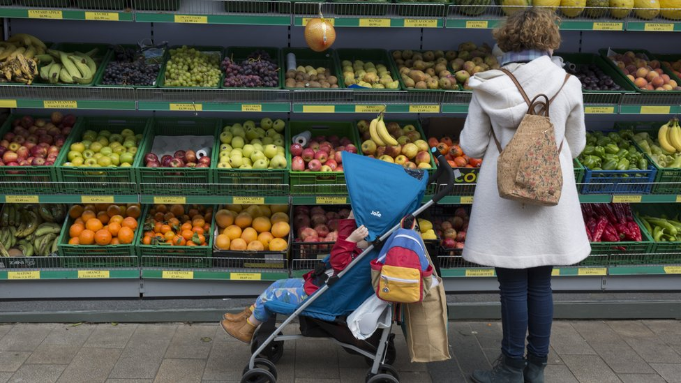 A woman and a child with a pram in front of shelves of fruit and vegetables