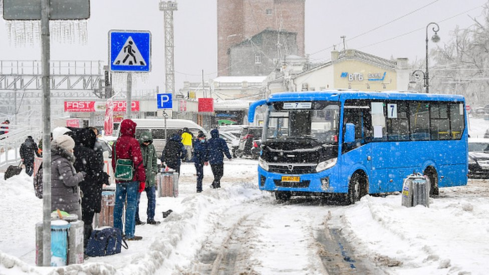 People wait at a bus stop during a snowstorm in Vladivostok