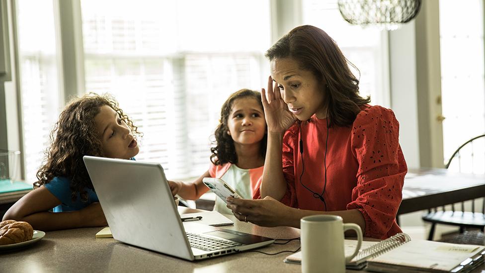 Una mujer tratando de trabajar con sus dos hijas al lado