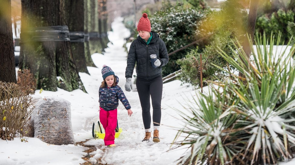 Lauren (L) and Anna Farnham take a walk through the snow in their neighborhood on December 9, 2018 in Charlotte, North Carolina