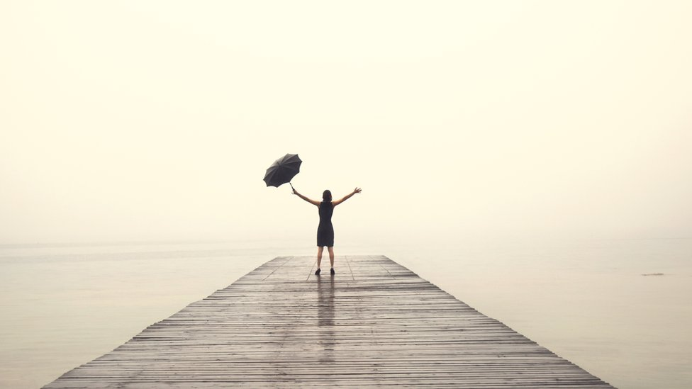 A woman wearing an elegant dress rejoices at the end of a pier, with their arms up in the rain and holding an umbrella