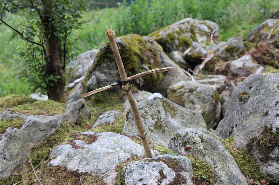 Wooden cross by some rocks