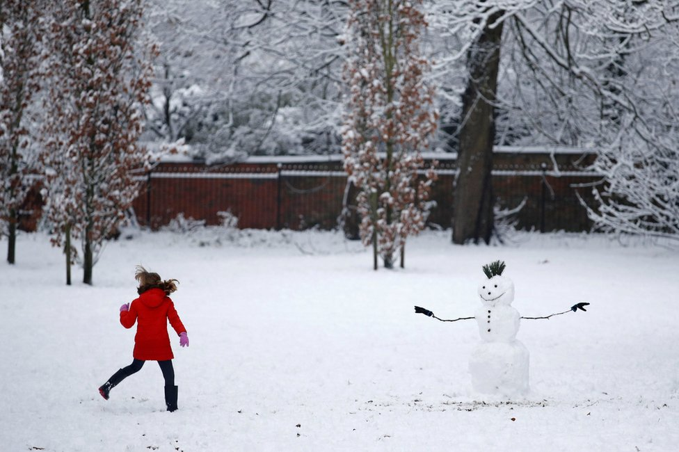 A child plays in the snow in Manchester