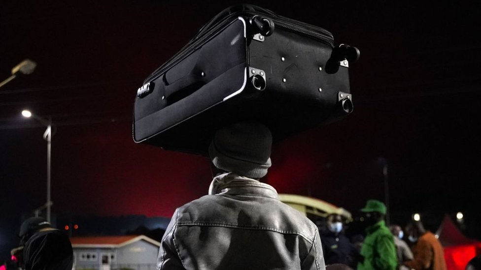 A person carries a suitcase on their head as Congolese people flee from Goma, DRC) after the Nyiragongo volcano erupted, on May 23, 2021